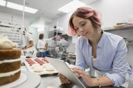 Pastry chef with digital tablet in commercial kitchen - HEROF29560
