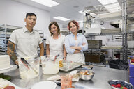 Portrait confident pastry chefs in commercial kitchen - HEROF29563