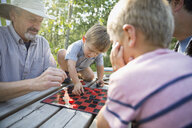 Multi-generation men playing checkers campsite picnic table - HEROF29593