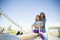 Mother and daughter playing on seesaw sunny playground - HEROF29644