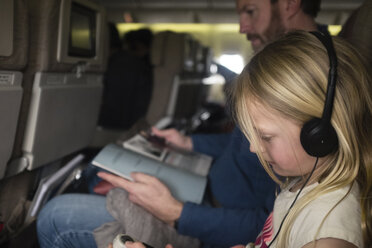 Side view of father reading magazine while daughter listening music in airplane - CAVF63157