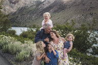 Romantic parents with cute daughters standing against mountain in forest - CAVF63181