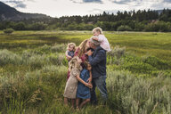 Romantic parents kissing while standing with daughters on grassy field against sky in forest - CAVF63211