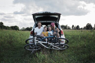 Happy family with bicycles sitting on car trunk amidst grassy field against cloudy sky - CAVF63229