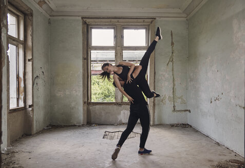 Man lifting ballerina while practicing ballet in old building - CAVF63256