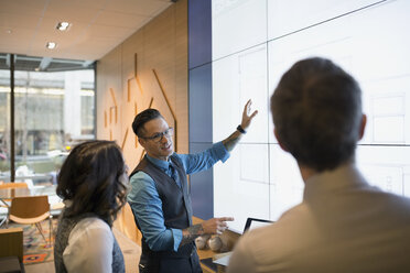 Architects discussing blueprints on projection screen conference room - HEROF29670