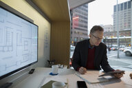 Architect with digital tablet drafting blueprints urban office - HEROF29679