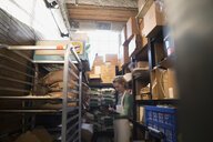 Bakery owner checking supplies inventory in storage room - HEROF29700
