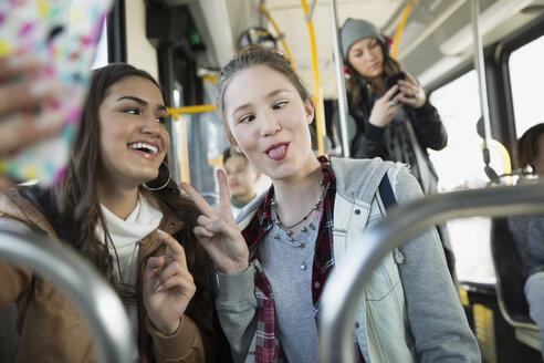 Teenage girl making a face taking selfie bus - HEROF29842