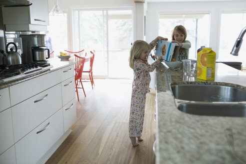 Sisters pouring cereal for breakfast in kitchen - HEROF29869