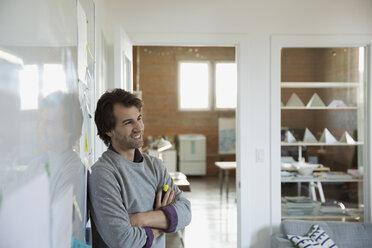 Smiling designer looking away at whiteboard in office - HEROF29878