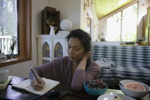 Woman writing in journal in living room - HEROF29890