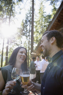 Smiling couple toasting wine and beer at wedding reception - HEROF29893