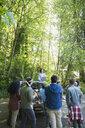 Woman guiding volunteers on tree planting in woods - HEROF29911