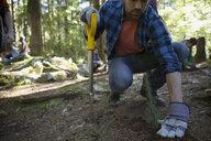 Volunteer planting trees in woods - HEROF29926