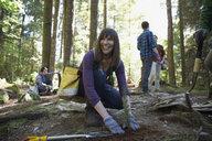Smiling volunteer planting tree in woods - HEROF29929