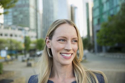 Smiling businesswoman looking away in city - HEROF29953