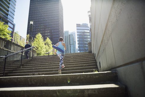 Woman with yoga mat ascending city steps - HEROF29959