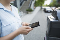 Woman using contactless payment on cell phone to pay for city parking - HEROF29968