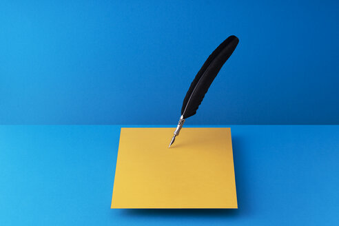 Quill pen writing on orange paper over blue background - DRBF00141