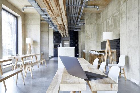 Laptop on wooden boards in modern office - FMKF05430
