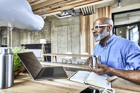 Mature businessman sitting at table in modern office with cloud balloon and laptop - FMKF05442