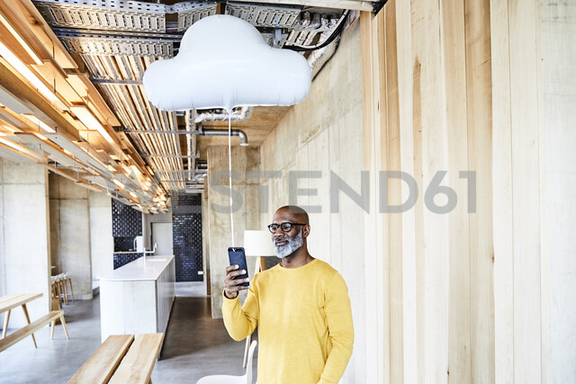 Mature businessman holding cell phone attached to cloud balloon - FMKF05445 - Jo Kirchherr/Westend61