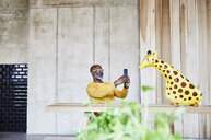 Mature businessman sitting at desk in office with cell phone and giraffe figurine - FMKF05454