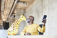 Mature businessman sitting at desk in office with cell phone kissing giraffe figurine - FMKF05457