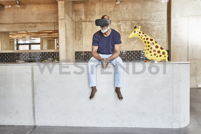 Mature businessman in modern office sitting next to giraffe figurine wearing VR glasses - FMKF05472