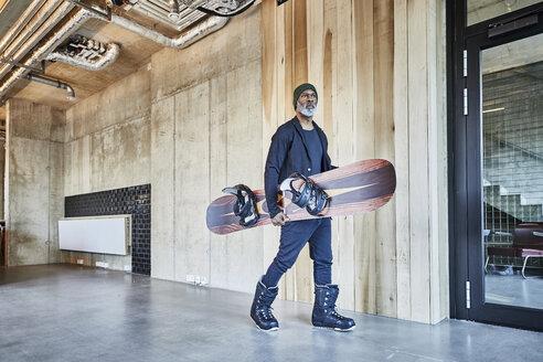Mature businessman holding snowboard in modern office - FMKF05484
