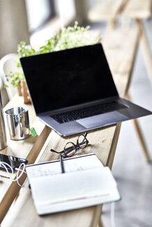 Notebook and laptop on wooden boards in office - FMKF05487