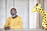 Mature businessman sitting at desk in office next to giraffe figurine - FMKF05499