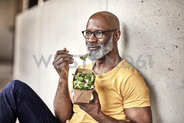 Mature businessman having lunch break eating a salad - FMKF05502