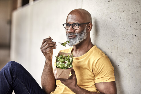 Mature businessman having lunch break eating a salad - FMKF05502