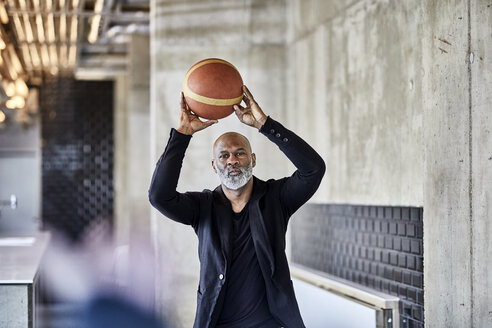 Mature businessman playing basketball in modern office - FMKF05505