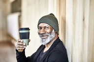 Portrait of happy mature businessman with takeaway coffee at wooden wall - FMKF05508