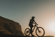Spain, Lanzarote, mountainbiker on a trip at sunset - AHSF00100