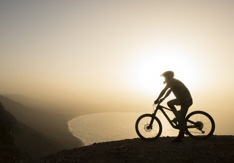 Spain, Lanzarote, mountainbiker on a trip at the coast at sunset - AHSF00106