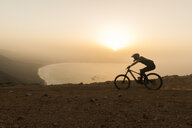 Spain, Lanzarote, mountainbiker on a trip at the coast at sunset - AHSF00112