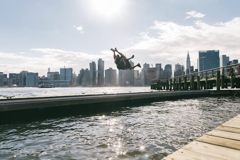 USA, New York, Brooklyn, two young men doing backflip on pier in front of Manhattan skyline - JUBF00338