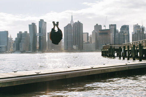 USA, New York, Brooklyn, young men doing backflip on pier in front of Manhattan skyline - JUBF00341