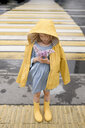 Girl wearing yellow rainjacket, standing on zebra crossing, holding lilac - EYAF00014