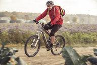 Man riding mountainbike on field ath - SEBF00055