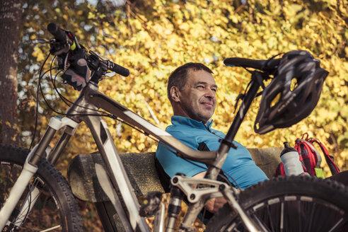 Man with mountainbike having a break sitting on a bench - SEBF00061