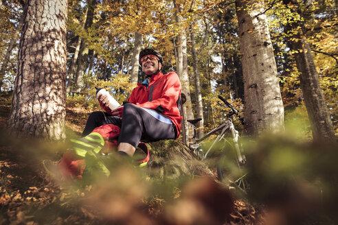 Man with mountainbike having a break in forest - SEBF00067