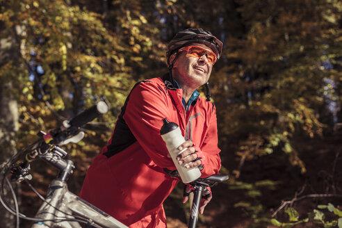 Man with mountainbike having a break in forest - SEBF00070