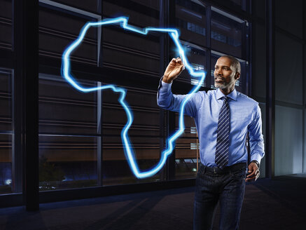 Businessman painting Africa with light - RORF01788