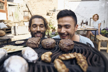 Friends preparing meat for a barbecue in the backyard - PDF01816