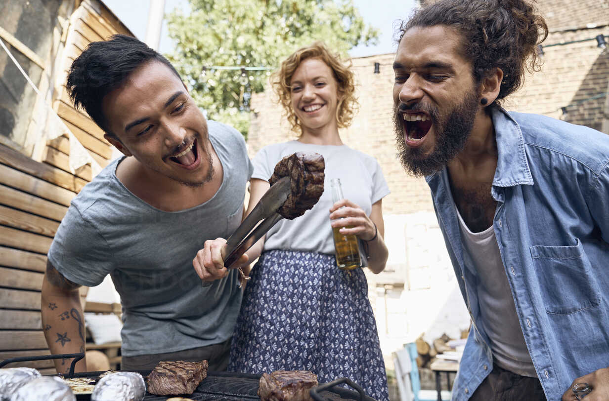 Friends having a barbecue n the backyard, preparing meat on a grill - PDF01822 - Philipp Dimitri/Westend61